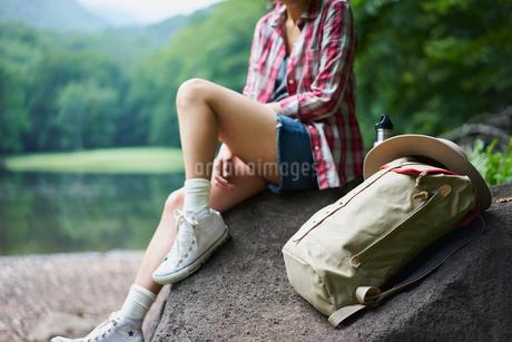 岩の上に座る女性とリュックサックの写真素材 [FYI02062213]