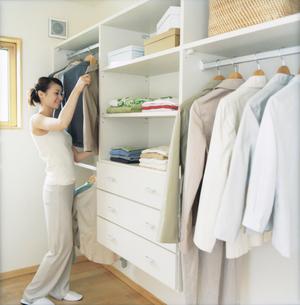 クローゼットで服を選ぶ女性の写真素材 [FYI02062225]