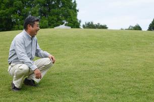 草原でしゃがむシニア男性の写真素材 [FYI02062291]