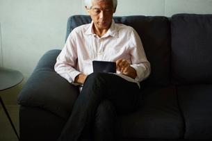 タブレットPCを操作するシニア男性の写真素材 [FYI02062370]