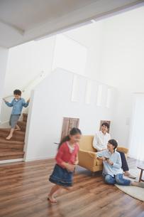 リビングルームで走り回る子供達とくつろぐ両親の写真素材 [FYI02062393]
