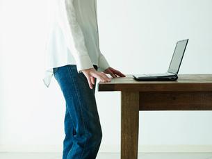 ノートパソコンとジーンズ姿の女性イメージの写真素材 [FYI02062403]