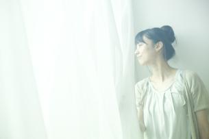カーテンを開け外を眺める女性の写真素材 [FYI02062463]