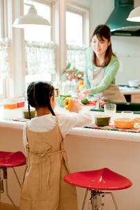 キッチンに立つ女の子と母親の写真素材 [FYI02062479]