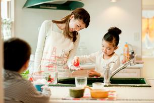キッチンでお手伝いをする女の子と母親の写真素材 [FYI02062487]