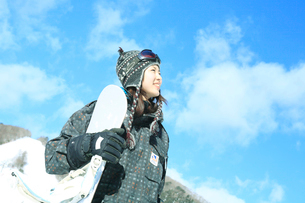 青空とスノーボーダー女性の写真素材 [FYI02062496]