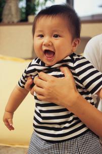 お母さんの手に支えられる赤ちゃんの写真素材 [FYI02062602]
