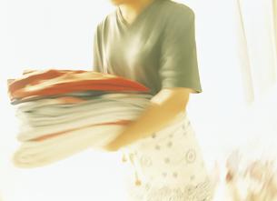 たたんだ衣類を運ぶ女性の写真素材 [FYI02062609]