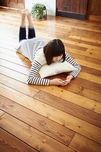 床に寝転びスマートフォンを操作する10代女性の写真素材 [FYI02062667]