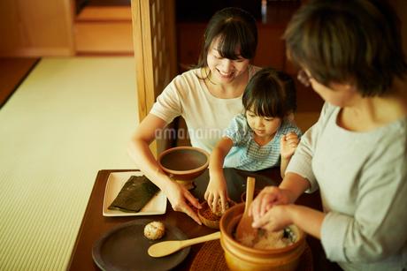おにぎりを作る三世代女性ファミリーの写真素材 [FYI02062680]