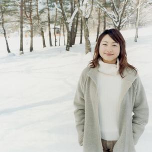 雪の林でコートを着た女性の写真素材 [FYI02062734]