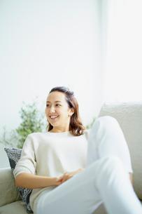 ソファでくつろぐ笑顔の女性の写真素材 [FYI02062774]