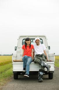 秋の田園で軽トラックに座る日本人カップルの写真素材 [FYI02062814]