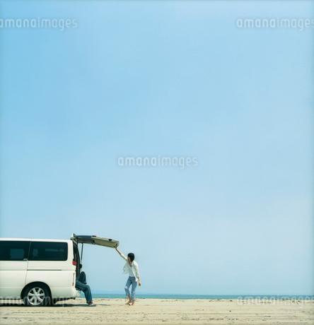 砂浜にとめた車と青空とカップルの写真素材 [FYI02062853]