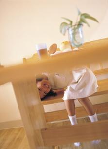 テーブルの下からのぞく女の子の写真素材 [FYI02062863]