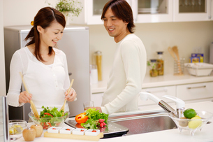 キッチンで料理をするカップルの写真素材 [FYI02062879]