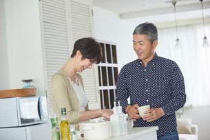 料理をするシニア女性とコーヒーカップを持ったシニア男性の写真素材 [FYI02062892]