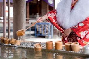 手水舎で柄杓を持つ振袖姿の女性の写真素材 [FYI02062930]