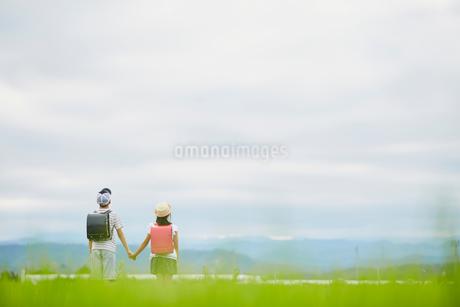 手をつなぐ小学生の兄妹と空の写真素材 [FYI02062990]