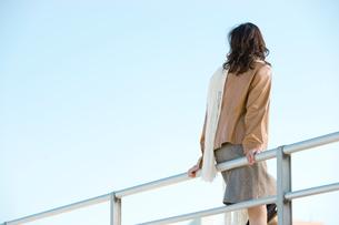 手すりにもたれる女性の後姿と青空の写真素材 [FYI02063048]
