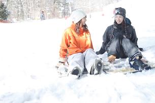 雪の上に座るスノーボーダー女性2人の写真素材 [FYI02063070]