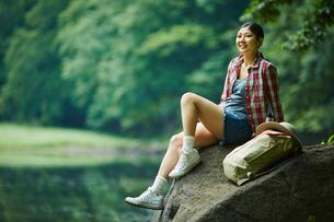 岩の上に座る女性とリュックサックの写真素材 [FYI02063112]