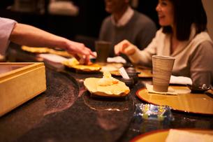 寿司屋で食事をする外国人カップルの写真素材 [FYI02063127]