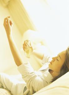 横になり手にコロンをつける女性の写真素材 [FYI02063163]