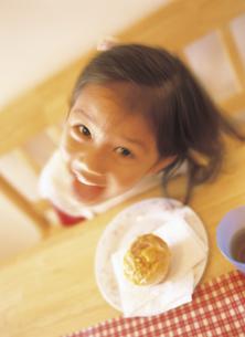 ダイニンクテーブルのお菓子と見上げる女の子の写真素材 [FYI02063171]