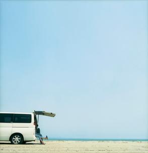 砂浜にとめた車と青空とカップルの写真素材 [FYI02063234]