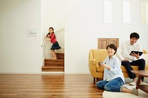 階段に立つ女の子とリビングルームでくつろぐ両親の写真素材 [FYI02063276]