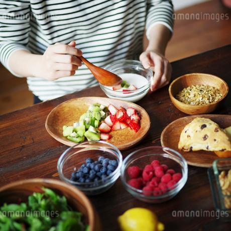 フルーツグラノーラヨーグルトを食べる女性の手元の写真素材 [FYI02063280]