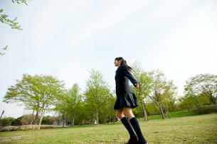 新緑の公園にいる女子中学生の写真素材 [FYI02063332]