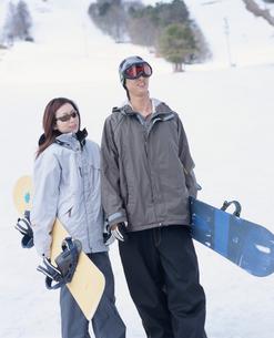スノーボードを持ったスノーボーダーカップルの写真素材 [FYI02063425]
