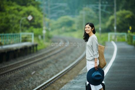 駅のホームに立つ女性の写真素材 [FYI02063435]