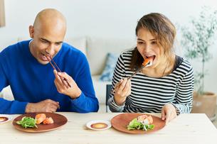 カリフォルニアロールを食べる外国人カップルの写真素材 [FYI02063453]