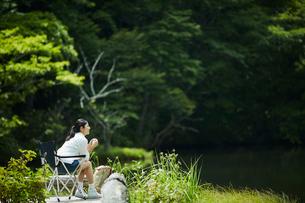 レジャーチェアに座りくつろぐ女性の写真素材 [FYI02063457]