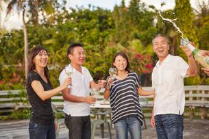 シャンパンシャワーを楽しむ2組の夫婦の写真素材 [FYI02063537]