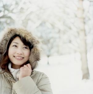 雪の林でフードを被る女性アップの写真素材 [FYI02063593]