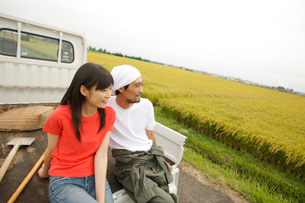 秋の田園で軽トラックに座る日本人カップルの写真素材 [FYI02063636]