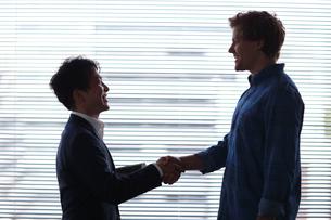 握手をする日本人ビジネスマンと外国人男性の写真素材 [FYI02063640]