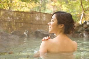 紅葉と露天風呂に入る女性の写真素材 [FYI02063645]