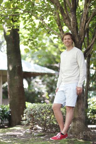 木にもたれる外国人男性の写真素材 [FYI02063672]