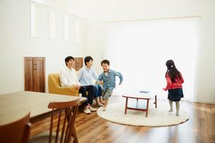 リビングルームで走り回る子供達とソファに座る両親の写真素材 [FYI02063690]