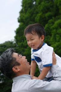 男の子を抱き上げるシニア男性の写真素材 [FYI02063699]