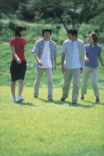 公園を歩く若者4人の写真素材 [FYI02063831]
