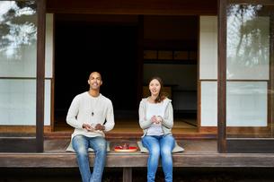 縁側でお茶を楽しむ外国人カップルの写真素材 [FYI02063865]