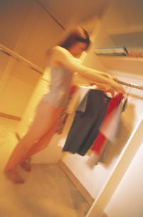 クローゼットの洋服を選ぶ女性の写真素材 [FYI02063871]