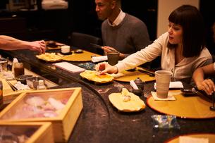 寿司屋で食事をする外国人カップルの写真素材 [FYI02063895]