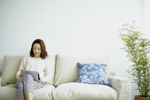 ソファに座りタブレットPCを見る女性の写真素材 [FYI02063903]